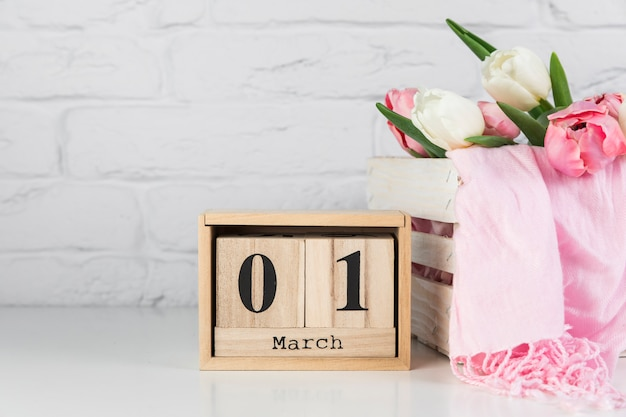 Wooden calendar with 1st march near the wooden crate with tulips and scarf on white desk