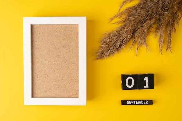 Wooden calendar with 1st september and pampas dry grass on yellow background with empty white frame