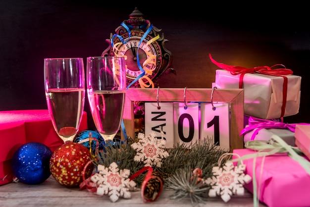 나무 테이블에 샴페인 잔과 새해 장식이 있는 나무 달력