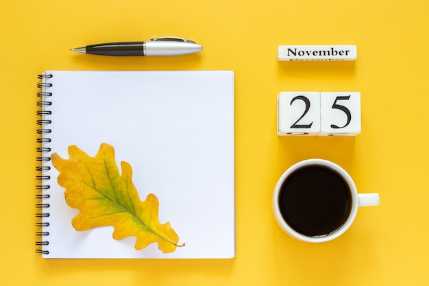 Wooden calendar with cup of coffee and notebook