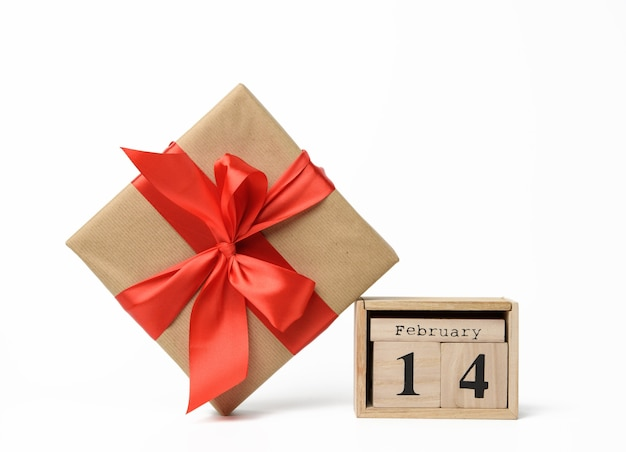 Wooden calendar with date 14 february and box with a gift on white background, valentine's day