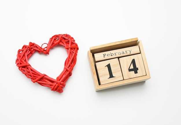 Wooden calendar with date 14 february and red heart on white surface, top view