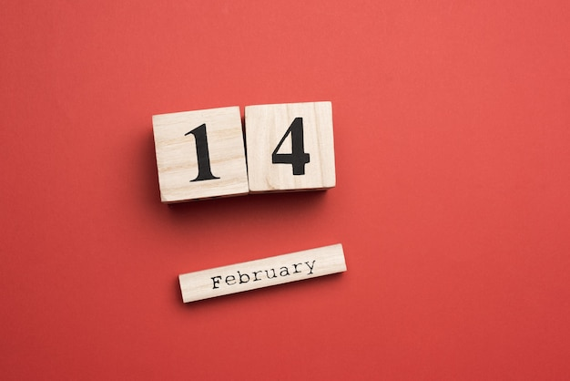 Wooden calendar with date 14 february on red, holiday valentine's day