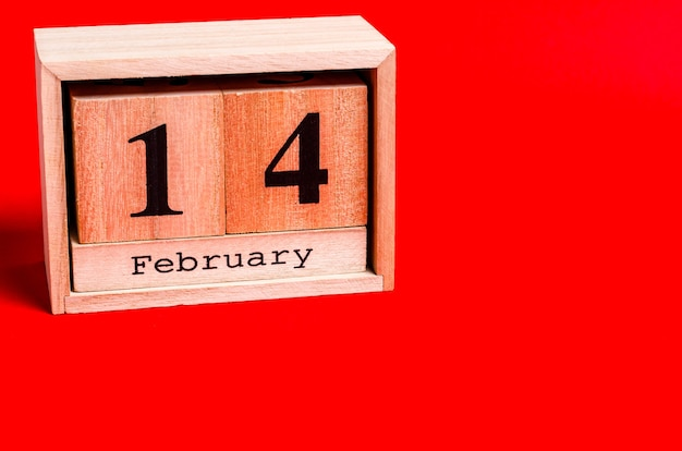 Wooden calendar with date 14 february on red