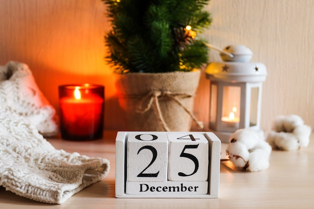 Wooden calendar with date december  against christmas festive background selective focus