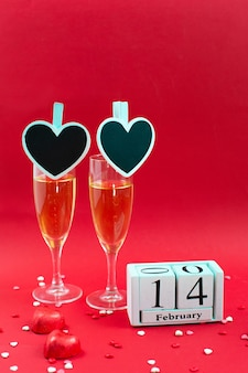Wooden calendar with date of february 14, candy and two champagne glass on red.