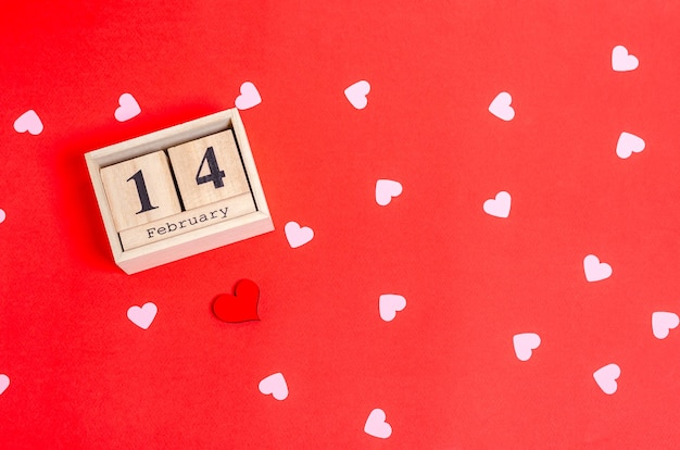 Wooden calendar with date february 14 and hearts pattern on red