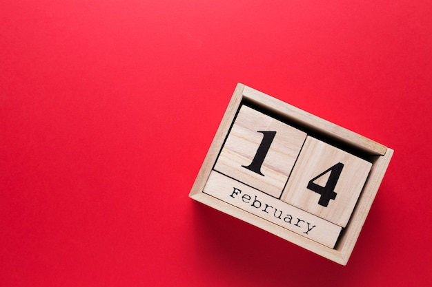 Wooden calendar with the inscription february 14 on a red isolated background.