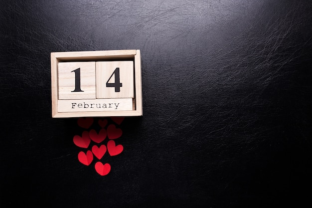 Wooden calendar with the inscription february 14 and with small hearts on a black isolated background.