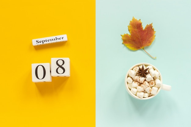 Wooden calendar with september 8th, cup of cocoa with marshmallows and yellow autumn leaves