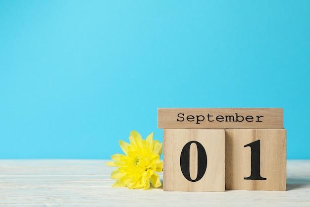 Деревянный календарь с сентябрем и хризантемами на деревянном столе, место для текста