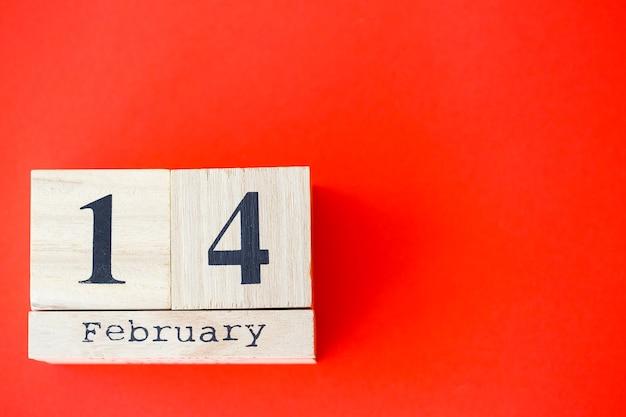 真っ赤な背景に2月14日の日付の木製カレンダー。ロマンチックなデート。バレンタインデーのコンセプト。上面図、コピースペース。