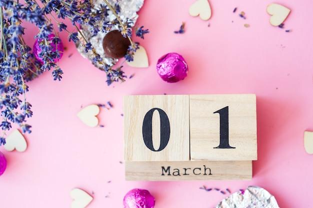 ピンクの背景に3月1日の日付の木製カレンダー、碑文の場所、春の初日、ラベンダーの乾いた枝