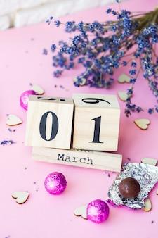 분홍색 배경에 3월 1일의 날짜가 있는 나무 달력, 비문을 위한 장소, 봄의 첫날, 라벤더의 마른 가지