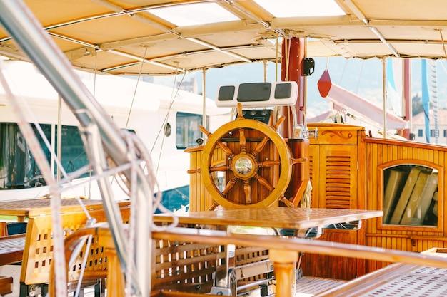 Деревянный капитанский мостик на белой яхте с красивым штурвалом и складными столиками