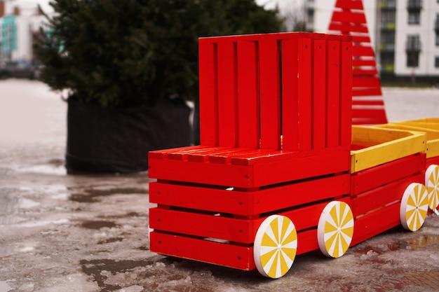 놀이터에 나무 자동차입니다. 겨울, 흐린 배경에 크리스마스 트리