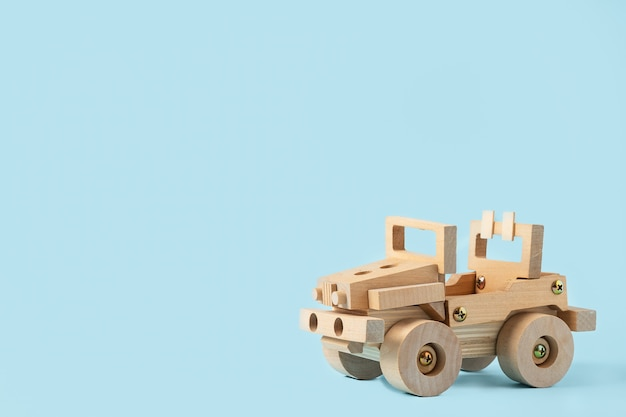 Wooden car toy with blue copyspace