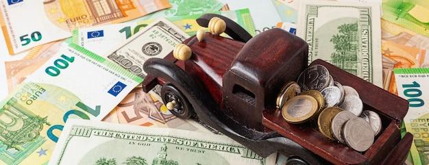 ユーロとドルのテクスチャ背景パノラマにコインと木製の車