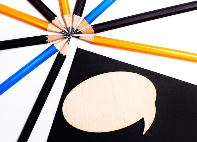Деревянная карточка с местом для вставки текста на черном фоне возле разноцветных карандашей. копировать пространство