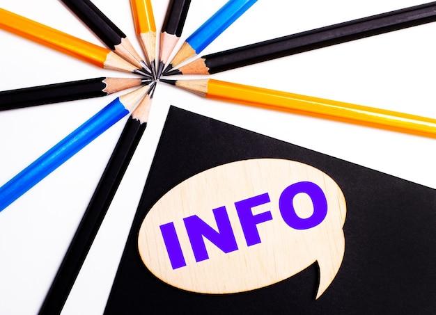 Деревянная карточка с текстом info на черном фоне возле разноцветных карандашей.