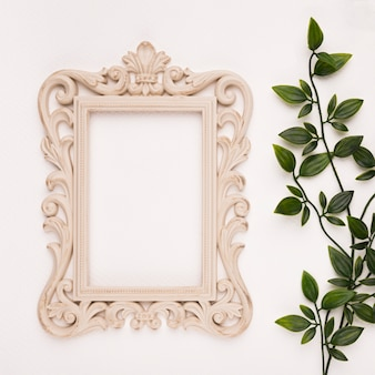 Wooden carving frame near the artificial leaves on white backdrop