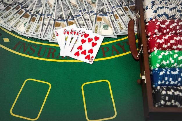 緑のテーブルにトランプと米ドルが付いたポーカーチップ用の木製ケース。ギャンブルの概念