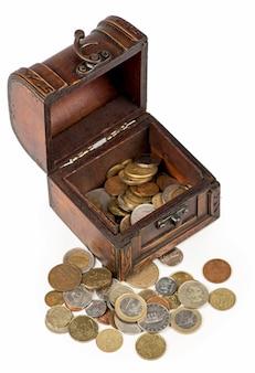 Деревянная шкатулка, полная тайских монет, изолированные на белом