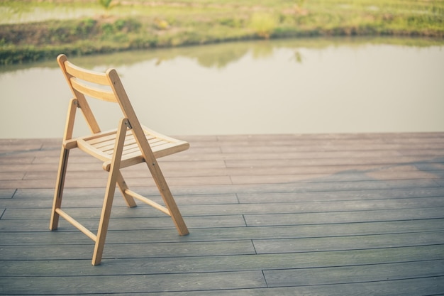 Wooden chair on balcony terrace patio for resting near pond