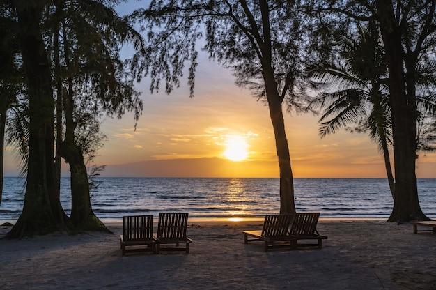 Деревянный стул рядом с пляжем с красивым идиллическим морским пейзажем и закатом на острове ко куд. ко куд, также известный как ко кут, - остров в сиамском заливе.