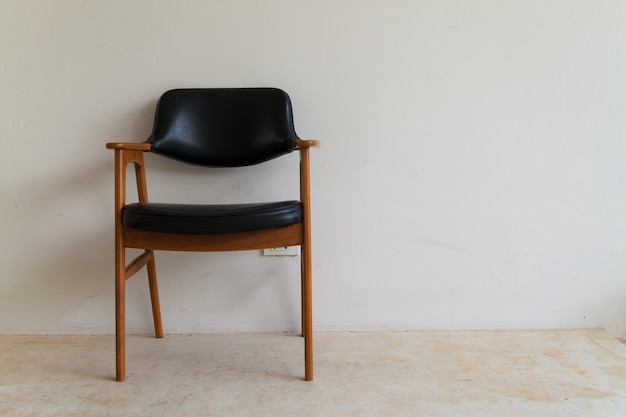 Wooden chair on concrete floor with white plain wall