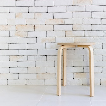 Wooden chair in empty white room against a brick wall