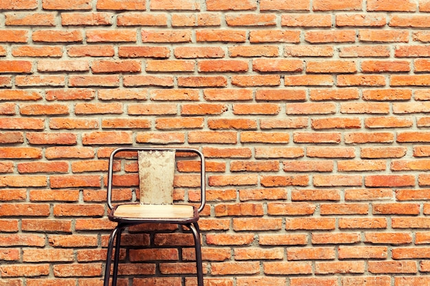 Wooden chair and orange brick wall background