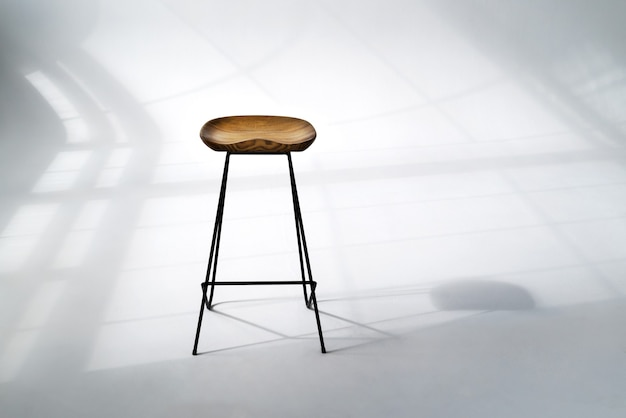 Wooden chair standing in the middle room with hard window frame shadows on white floor