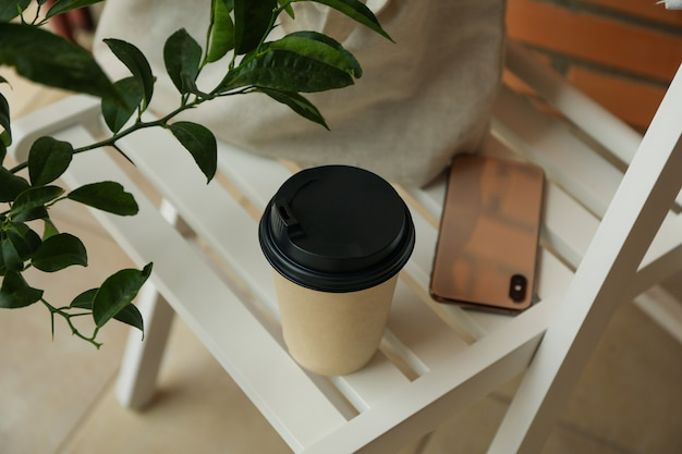 Wooden chair with cotton bag, phone and paper cup