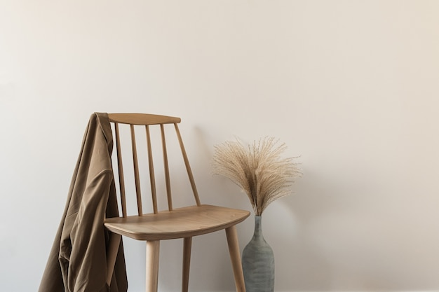 シャツ、白い壁に花瓶のパンパスグラスと木製の椅子。