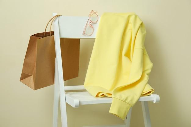Деревянный стул с желтой толстовкой, сумкой и очками