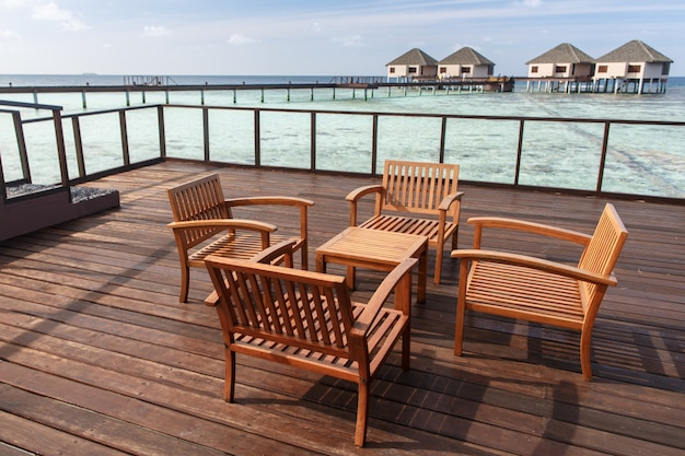 Wooden chairs at balcony with water villas background