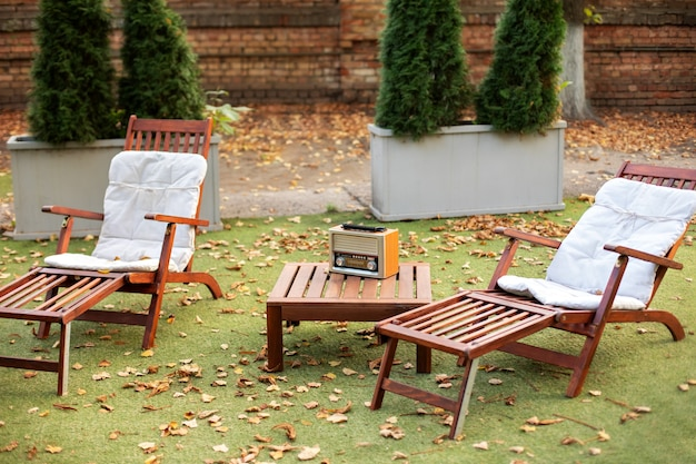 Wooden chairs in garden. two deckchairs on lawn on picnic.