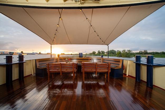 Sedie in legno e tavoli con fiori e lanterne in cima alla barca