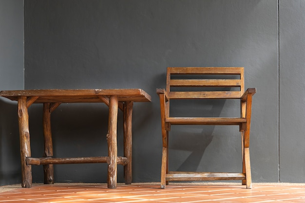 Wooden chairs and wooden tables are placed on terracotta tiles and plaster walls painted gray