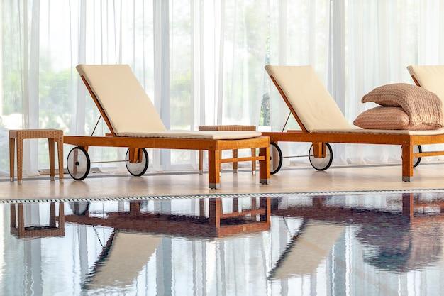 가정용 실내 수영장의 넓은 창문에 매트리스가 있는 나무 의자 라운지