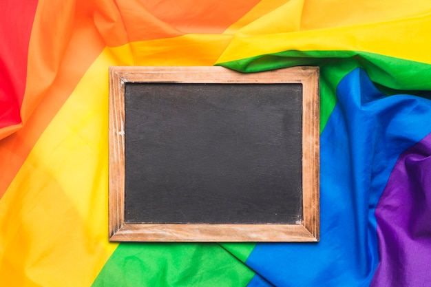 Wooden chalkboard and crumpled lgbt flag