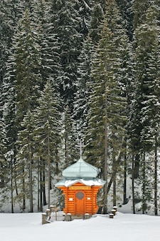 雪に覆われた森の中にある木造の礼拝堂