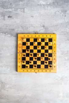 Wooden chess board and making chess move, flat lay