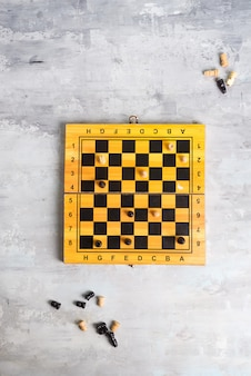 Wooden chess board and making chess move on stone, flat lay