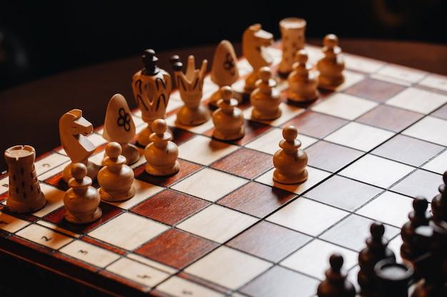 チェスの駒が付いている木製のチェス盤