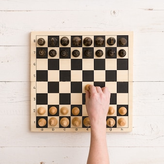 Wooden chess board with figures ready for the game and mans hand making his first chess move