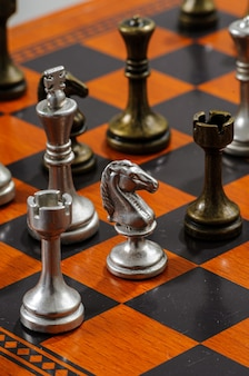 Wooden chess board with metal pieces. checkmate.