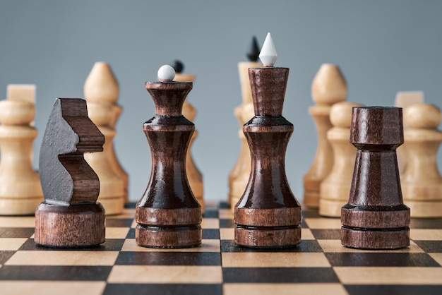 Wooden chess pieces on a chessboard, black pieces in a row, white pieces in the background, concept, strategy, planning and decision making