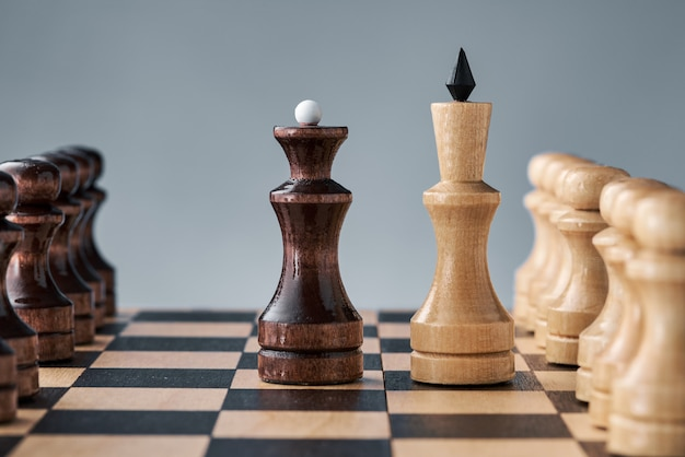 Wooden chess pieces on a chessboard, the confrontation of the white king and the black queen, the concept of planning and decision-making